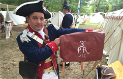 Re-Enactment Soldier Holding a Brown Canvas Bag